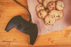 Gamepad and homemade chocolate chip cookies on rustic wooden tab - stock photo