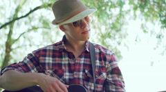 The young man in hat playing the guitar in sunny green park. 4k Stock Footage