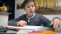 Child sit at the desk while choosing colour for his drawing Stock Footage