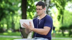 Man with white tablet computer sits on the bench in city park Stock Footage