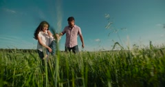 Happy Asian family with small child 1 year running on the green field, slow Stock Footage