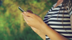 Close up of girl's hands using phone in the green summer park. 4k Stock Footage