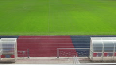 Football field and benches for spare players from the tribunes - stock footage