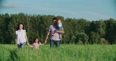 Young happy Asian family goes on a green field with two children, slow motion Stock Footage