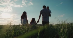 Young happy Asian family goes on a green field with two children, slow motion Arkistovideo