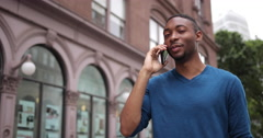 Young African American black man in city talking on cell phone Stock Footage