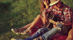 Two girl with funny boy rejoicing with guitar on the nature. 4k - stock footage