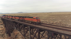 AERIAL: Train crossing steel arch railroad bridge across the Canyon Diablo Stock Footage