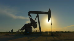 Industrial jack pump platform pumping crude oil over sunset sun Stock Footage