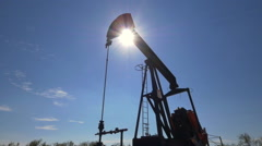 Industrial jack pump working on oil field over the sun Stock Footage