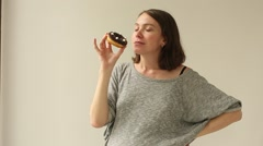 Woman biting chocolate donut on a white background Stock Footage