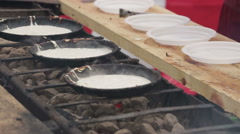 The pancakes are fried in a pan on the coals Stock Footage