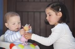 Brother and sister playing with dolls. Sex stereotyping overcome Stock Photos