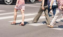 legs of pedestrians crossing the road - stock photo