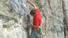 4K Young man climbing vertical rock face trying to find a strong grip - stock footage