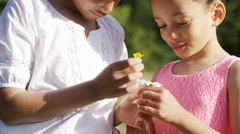 4K Two young girls look at flowers together in a field Stock Footage