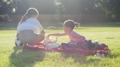 4K Two young children sit down to have a picnic in the sunlight, in slow motion  Stock Footage