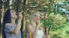 Happy girls blowing soap bubbles in summer park. Slowly - stock footage