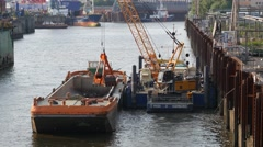 Excavator digging mud out of the harbor channel in Hamburg port Stock Footage