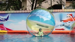 Kids in zorb bubble ball swimming in pool - stock footage