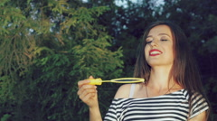 Happy brunette blowing colourful soap bubbles in summer park. Slowly - stock footage