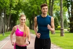 Attractive two joggers competing with joy - stock photo