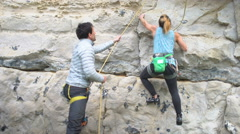 4K Female climber ascending vertical rocky face assisted by male partner Stock Footage