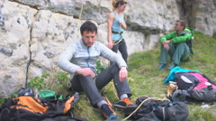 4K Group of active friends chatting as they prepare to climb vertical rock face  Stock Footage