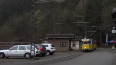 Two-car old yellow tram arrives to the Lichtenhainer Wasserfall terminus station Stock Footage