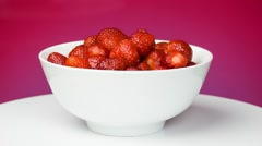Strawberries in a white bowl rotation. Pink background Stock Footage