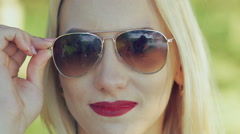 Sexy blonde with claret lips gets off sunglasses. Slowly Stock Footage