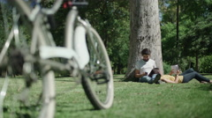 Young couple in love chilling in the park. Dolly shot - stock footage