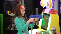 Little girl playing shooter video game in game center Stock Footage