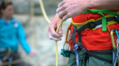4K Rock climber attaching rope to his harness in preparation to climb Stock Footage