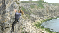 4K Young woman climbing rocky cliff on the English coastline.  Stock Footage