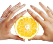 Manicure pedicure on afro-american tann skin hands holding orange, healthcare Stock Photos