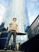 real young man stand in front of modern business building - stock photo