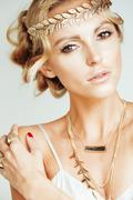 Young blond woman dressed like ancient greek godess, gold jewelry close up Stock Photos