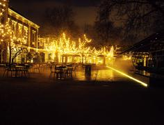 Empty night restaurant, lot of tables and chairs with noone, magic fairy lights Stock Photos