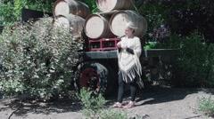 Woman Drinks Wine near Casks on a truck in the   wind - stock footage