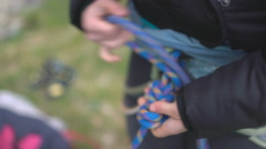 4K Rock climber attaching rope to her harness in preparation to climb Stock Footage