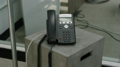 An office phone sits on a cinderblock, over a pile of smartphones on the floor. Stock Footage