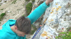 4K Male rock climber beginning a climb on rocky cliff face Stock Footage