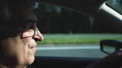 Senior driving a car at sunset. Close up Stock Footage