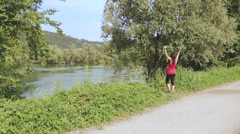 Beautiful woman rising her hands and nordic walking poles on the riverside Stock Footage