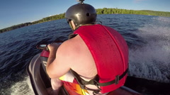 Action Seadoo rider racing around the lake on his pleasure craft Stock Footage