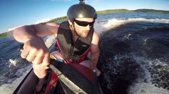 Action Sports Jet Ski Seadoo rider racing around the lake on his pleasure craft Stock Footage