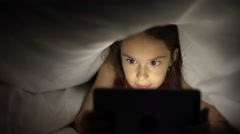 Little girl uses the tablet in bed before going to sleep Stock Footage