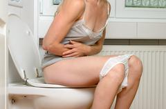 Woman with a stomach ache sitting on a toilet Stock Photos
