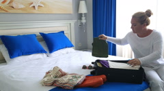 Woman in hotel room packing suitcase 2 - stock footage